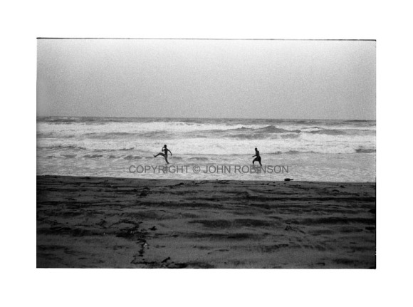 Two men running in the shallows.