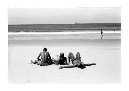 Three youths in the sun, a ship, a beach walker and man swiming