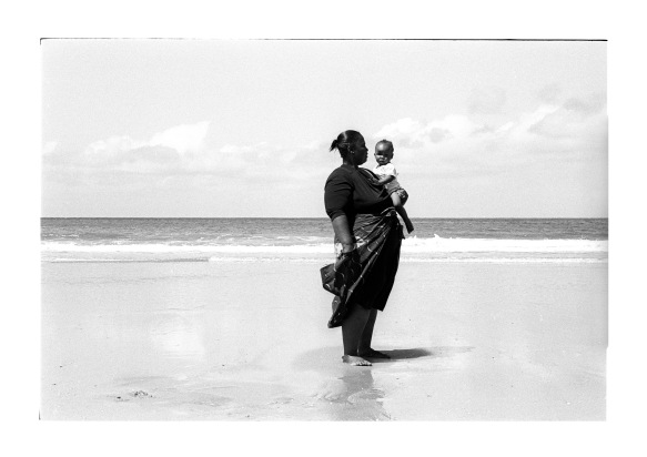 A woman and a little girl stand in wet sand