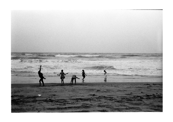 Five children playing on sand.