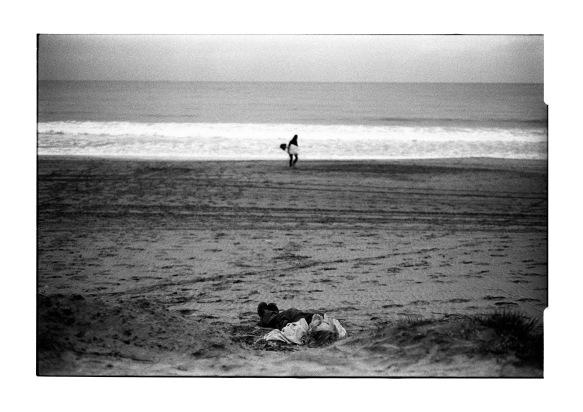 Surfer walks past man sleeping in night light.