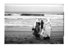 Three sangomas praying and clensing in sea water.