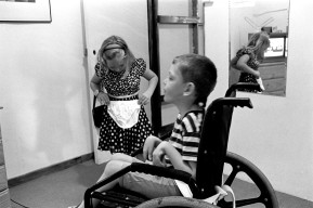 Louis' sister stands and models her new underclothes while he sits in his wheelchair