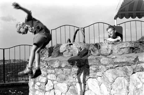 Louis looks on as a friend jumps off a wall at Hope School.