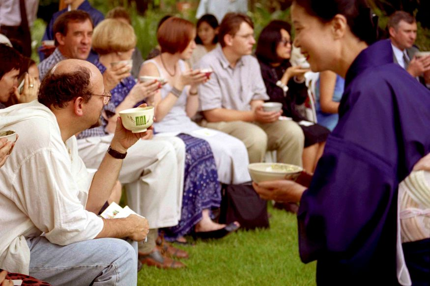 ipjr01185430 Japanese Tea Ceremony A photographic series by John Robinson 1999 Blair Athol Johannesburg South Africa The hanto or assistant to the host offers tea to the guests. Taking the tea scoop and tea container, the teishu or host places three portions of tea per guest into the tea bowl. Hot water is ladled from the kama into the teabowl to create a thin paste with the whisk. More water is then added to so the paste can be whisked into a thick liquid much like a pea soup. Unused water in the ladle is returned to the kama. The tea bowl is passed from the teishu to the principal guest who bows in accepting it. The bowl is raised and admired, the guest will then drink some of the tea, wipe the rim of the bowl, and pass the bowl to the next guest who will then raise and admire the bowl before sipping the tea. When all the guests have shared the tea the bowl is returned to the host who rinses the bowl, whisk and tea scoop. The tea container is then cleaned. The chashaku and tea container are presented to the guests for examination. The objects, presentation and other appropriate topics are then discussed. ©John Robinson/South Photographs africa afrika afrique asia orential japanese culture chasen chawan hishaku futaoki fukusa