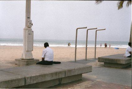 Durban in off season, two people sit beside the unused showers on Wedge Beach. September 2016, Durban, South Africa, John Robinson