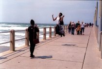 Durban in off season. Young woman jumps into the air on North Pier for a friend's photograph. September 2016, Durban, South Africa, John Robinson