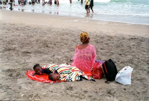 Durban in off season. Mother and two children relax on South Beach while others swim in the sea. September 2016, Durban, South Africa, John Robinson
