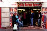 Durban's People. Ally comes from Barundi, he sits with his wife and daughter outside his shop, Ally Barber Salon, Alexandra Street, Durban, South Africa.
