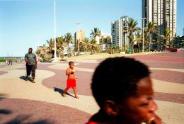 Durban beachscapes. Kids eating fruit, and walking in the winter sun on the Wedge Beach promenade, Durban, South Africa.
