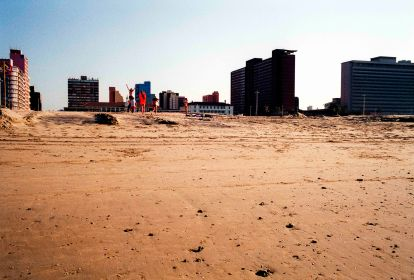 Durban beachscapes. Holiday makers play touch rugby on Durban's wide beach sands, with Addington Hospital in the background, Durban, South Africa.