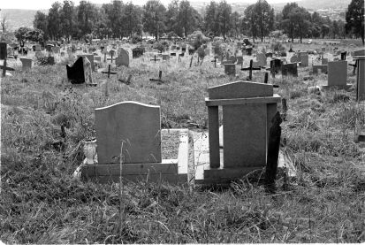 Tombstones and simple wooden crosses in the mountain rise grave yard.