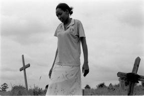 A daughter looking for her mother's grave among the wooden crosses marking other resting places of the dead.