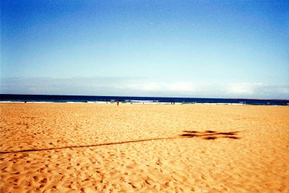 Durban beachscapes. The shadow of a towering flood light stretches out across the pock marked sand of Wedge Beach, Durban, South Africa.