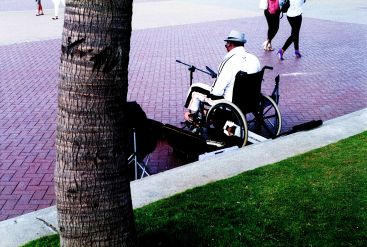 Beachscapes, people walking on past a paraplegic busker on the Durban promenade.