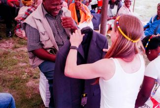 A daughter of the groom gives a suit to Imbali Nxumalo's father as part of the bride price that Douglas Wood paid for his wife to be.