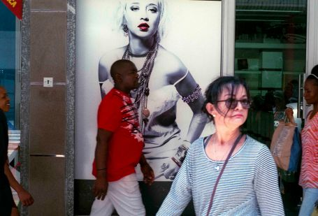BESETdurban, people walk past a retail poster in a down town shop window. Durban, South Africa.