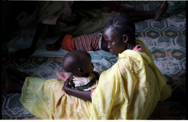 "ipjr09440306 September 2004 Gebeiaulia IDP Camp Khartoum Al Khartoum Sudan Mother and child at Gebeialia IDP Camp. Gebeiaulia IDP Camp is about 35 kms from the city of Khartoum. the IDP camps around the city have been bulldozed and are being moved away from the city, as the ""land has been zoned for other use"" ©John Robinson/MCC/South Photographs africa afrika afrique arab african genocide janjaweed milita armed horsemen. refugees refugee"