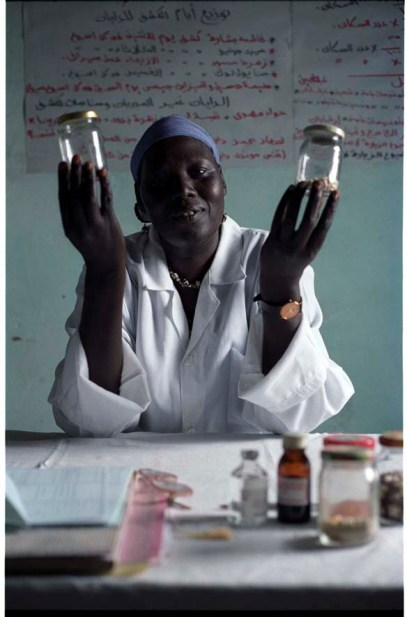 """ipjr09440310 September 2004 Gebeiaulia IDP Camp Khartoum Al Khartoum Sudan The midwife at the camp with bottles of beans illistrating good nutrition. Gebeiaulia IDP Camp is about 35 kms from the city of Khartoum. the IDP camps around the city have been bulldozed and are being moved away from the city, as the """"land has been zoned for other use"""" ©John Robinson/MCC/South photographs africa afrika afrique arab african genocide janjaweed milita armed horsemen. refugees refugee"""