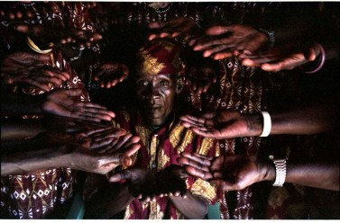 """ipjr09441634 September 2004 Rumbek Al Buhayrat Sudan The New Sudan The face of the choir master and the hands of the members of the choir. The returned people, the war in the south of the Sudan has been around for 50 years. The Rumbek Peace Choir was formed out of five local choirs, each contributing a few members. """"music is like a newspaper, through our music we communicate the message of peace"""" ©John Robinson/MCC/South Photographs africa afrika afrique sudan The New Sudan war refugee refugees returned exiles exile education reconstruction villagers villager village food"""