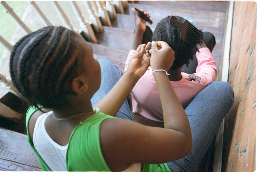 ipjr11049437 urban youth, programs, shelters two girls sit on steps as one braids the hair of her friend in pietermaritzburg kwazulu-natal south africa durban/pietermaritzburg kwazulu-natal south africa copyright © john robinson/south photographs africa afrika afrique people social documentary reportage majority world developing world third world children teens kids urban shelters street