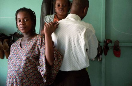 """A Congolese man (with back to camera) with his sister and child. """" please do not show my face as I am afraid"""" He lives as a refugee with his family in Durban South Africa. November 2007 DURBAN SOUTH AFRICA PHOTO JOHN ROBINSON"""