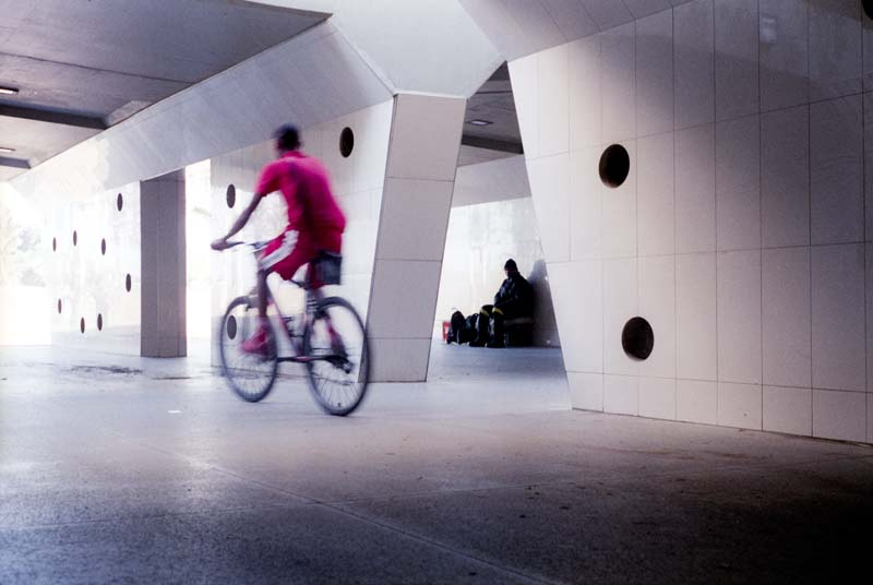 A man goes through an underpass of the M4 freeway on a bicycle on a sunday afternoon