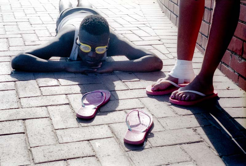 Man lieing on paving with swimming goggles, plastic sandals and friend's sore foot.