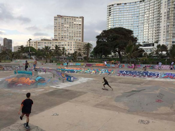 The North Beach Skatepark at 29,50.7347S and 31,2.1872E is a part of the Durban skateboard, push scooter and BMX bicycle riders world. These riders are the whippets of the urban pavement, hated by some in the city and looked up to by others. These riders view the city's concrete and steel as just surfaces to jump, glide and skid over. This Durban sub culture perfect their street credentials on a painted concrete backdrop of some of Durban's street artists doing. The skatepark is situated between the Bay of Plenty beachfront and the trees of a Durban sunken gardens. The whole area is looked over by the sky reflecting windows of hotels and beach front apartments. The Durban skatepark is often used by film and video producers for location shoots as South Africa is US Dollar friendly and the skatepark can double for locations set on the American mainland and elsewhere.