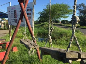 During Covid 19 lockdown, grass growing back over benches and swings in Merewent, Durban
