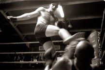 ipjr08360110 Fight Club - A Picture Story by John Robinson 11 May 2003 Pietermaritzburg South Africa David yates kicks Carl Webster on the ground. High kicks and punches smack into bodies as the fighters compete, the seconds shout instructions to their fighters, the fancy outfits that clothed their men on that walk from the change rooms count for naught once the clash begins. Only hard kicks will stop the other man. The meek might gain the world, but here only the hardest man will get the purse. ©John Robinson/South Photographs africa afrika afrique sport kick boxing fight tournament
