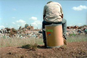 A young man sits on a cardboard bin wearing his school passing-out shirt at the start of a days plastic picking, South Africa has a high unemployment rate and for many young people working a city landfill site is the only source of income.