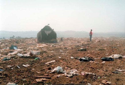 Figure in a landscape, a municipal worker pauses in the waste and debris of his daily workplace.