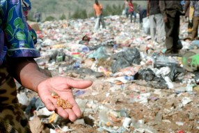 A woman produces a gold pendant and chain that she found in the carpet of plastic that is this landfill site in South Africa.