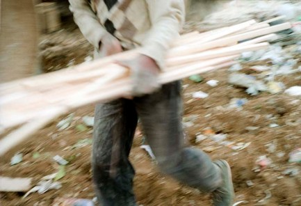 A man carries away wood offcuts, many of these people live in informal shacks near or on the landfill site. This wood could be part of his small home by nightfall.