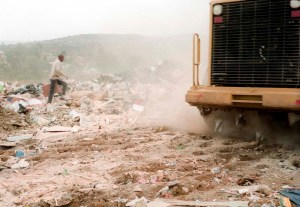 A waste picker runs after a grader to sift through waste. Whole families are supported by men and women who spend their days collecting what other people consider worthless.